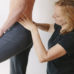 Physiotherapist palpating the lower back of a standing patient.