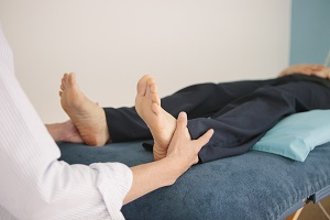 Therapist touching the feet of a patient during a Craniosacral Therapy session.