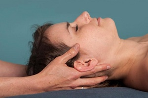A patient's head rests on the hands of a therapist during a Craniosacral Therapy session.