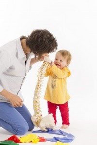 Mom physiotherapist with laughing baby, showing her a model of a spine